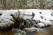 Stream in forest after a fresh dusting of snow in Lincoln, New Hampshire USA.