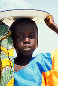 The Gambia. Girl carrying a plastic bag on an enamel plate on her head.