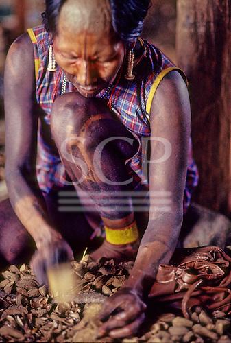 A-Ukre village, Xingu, Brazil. Kayapo woman with black body paint crushing Brazil nuts.