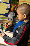 Education Preschool 3-4 year olds boy talking as he plays with two small dollhouse dolls