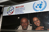 Two Brazilians, a man and a woman, smiling below a sign for the conference. United Nations Conference on Sustainable Development (Rio+20), Rio de Janeiro, Brazil, 13th June 2012. Photo © Sue Cunningham.