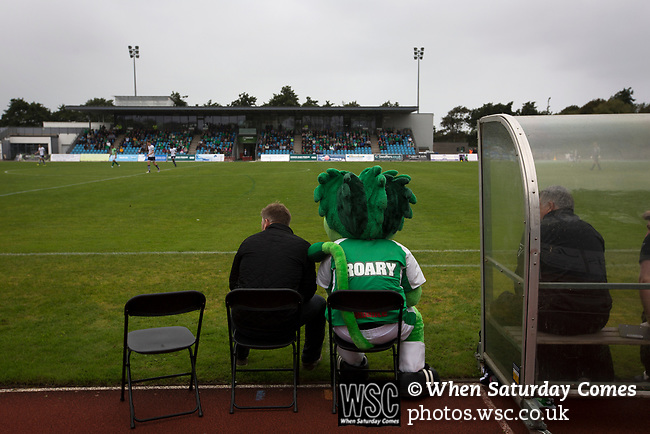 Guernsey 0 Corinthian-Casuals 1, 10/09/2017. Footes Lane, Isthmian League Division One. Mascot Roary the Lion sitting on the home bench next to the club's manager as Guernsey (in green) take on Corinthian-Casuals in a Isthmian League Division One South match at Footes Lane. Formed in 2011, Guernsey FC are a community club located in St. Peter Port on the island of Guernsey and were promoted to the Isthmian League Division One South in 2013. The visitors from Kingston upon Thames won the fixture by 1-0, watched by a crowd of 614 spectators. Photo by Colin McPherson.