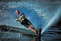 A waterskier lays over in a turn and sprays a wall of water. sports. Dave Weigand. Utah, Utah Lake.