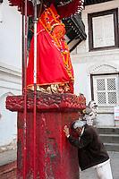 Nepal, Kathmandu.  Elderly Man Worshiping at Hanuman Statue, Durbar Square.