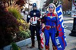 "Trump supporters dressed in super hero costumes watch as anti-Trump protesters march during the ""Million MAGA March"" on November 14, 2020 in Washington, D.C.  Thousands of supporters of U.S. President Donald Trump gathered to protest the results of the 2020 presidential election won by President-Elect Joe Biden.  Photograph by Michael Nagle"