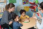 Education Preschool classroom scenes 2 year olds boy and girl working with speech therapist, therapy intern looking on