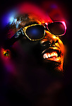 """This is a portrait that was heavily worked in Photoshop after publication of the unretouched image. CBS aired a special tribute to Stevie Wonder February 16, 2015 called """"We all know that face of Stevie Wonder the Motown phenom. But photographing him in a step down office under a Beverly Hills building was a challenge because the dark walls with pipes running up the walls made it almost impossible to find a background that would not be distracting. But having Mr. Wonder singing only for this photographer and Mr. Wonder's agent was a surreal experience. The original was shot on the ultra fine grain 25 ISO Kodak film. Long after publication in the Los Angeles Times, the reflection of a stobe light box with a yellow filter in a his glasses was removed and the other two colors of gelled lights were modified by hue and blurred. In addition to the colored lights one with a white light coming straight into the picture keeps the natural skin tones and his teeth appear correct in color."""