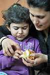 Gabriela Iseni, 4, a Roma girl whose family was displaced by a severe cold spell, eats a meal, with help from her mother, Juntena Iseni, in a temporary shelter established by the Red Cross in Smederevo, Serbia. Church World Service has provided this family and others with food and other emergency supplies.