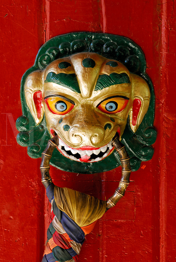 Animal protector with colored silk scarves on the entrance door to the Summer Palace, or Norbulingka, founded by 7th Dalai Lama in 1755, Lhasa, Tibet, China.