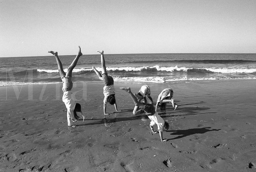 Kids doing handstands on the beach
