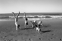 Kids doing handstands on the beach