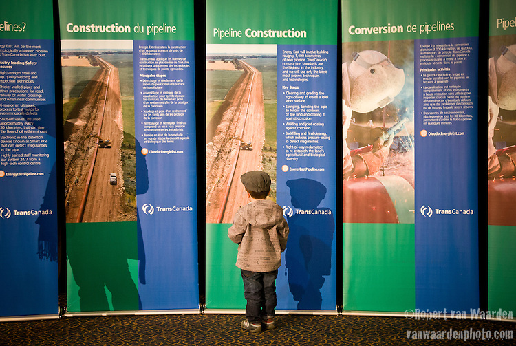 A young boy examines the TransCanada Energy East pipeline information during the Open House event in Montreal.