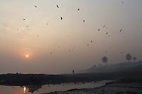 A young boy stands on the banks of the Ganges River at sunrise. This stretch of the river is now regarded as the most polluted in its entire length, as a result of the local leather tannery industry which dumps its water waste directly into the river.