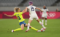 TOKYO, JAPAN - JULY 20: Megan Rapinoe #15 of the United States battles with Amanda Ilestedt #13 of Sweden during a game between Sweden and USWNT at Tokyo Stadium on July 20, 2021 in Tokyo, Japan.
