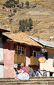 Puno, Peru. Rural Quechua woman in traditional dress sitting on steps outside a small restaurant with traditional building and mountain..