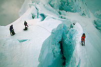 Three climbers standing on ice and snow using ropes across a crevasse while making an ascent of Huascarin, the highest peak in the Tropics, Peru.