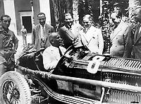 Benito Mussolini driving an Alfa Romeo racing car. In the center Prospero Gianferrari. circa 1931.