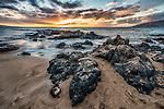 A sunset viewed from the beach over volcanic rocks at Kamaole Beach Park III, Kihei, Maui, Hawaii