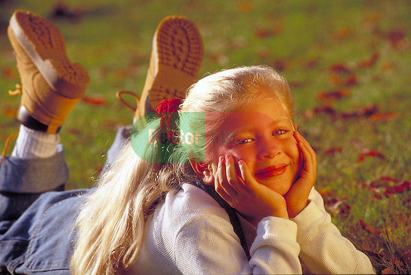 portrait of smiling young girl lying on grass