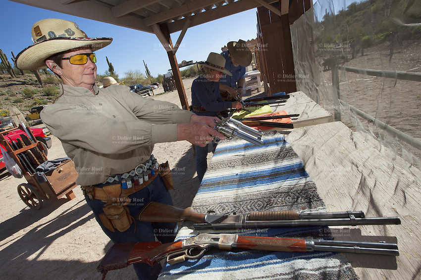 """USA. Arizona state. Peoria. Peoria is distant 50 km from Phoenix. Cowtown Shooting Range. Cowtown Cowboy Shooters Association. Fake town scenery from the old Far West time. A group of elderly women and men, all dressed with cowboys outfits, train outdoors for the incoming Winter Range - SASS National Championship of Cowboy Action Shooting ( february 22nd-28th, 2016). The Single Action Shooting Society (SASS) is a Cowboy Action Shooting (CAS, also known as Western Action Shooting, Single Action Shooting, or Cowboy 3-Gun). CAS is a type of multi-gun match utilizing a combination of pistol(s), rifle ( Winchester), and/or shotgun in a variety of """"old west themed"""" courses of fire for time and accuracy. Participants must dress in appropriate theme or era """"costume"""" as well as use gear and accessories as mandated by the respective sanctioning group rules. A CAS shooter engages a target with his lever-action rifle. Cowtown Shooting Range is a semi-private outdoor shooting range and firearms training facility. A firearm is a portable gun, being a barreled weapon that launches one or more projectiles often driven by the action of an explosive force. Most modern firearms have rifled barrels to impart spin to the projectile for improved flight stability. The word firearms usually is used in a sense restricted to small arms (weapons that can be carried by a single person). The right to keep and bear arms is a fundamental right protected in the United States by the Second Amendment of the Bill of Rights in the Constitution of the United States of America and in the state constitutions of Arizona and 43 other states. 31.01.16 © 2016 Didier Ruef"""