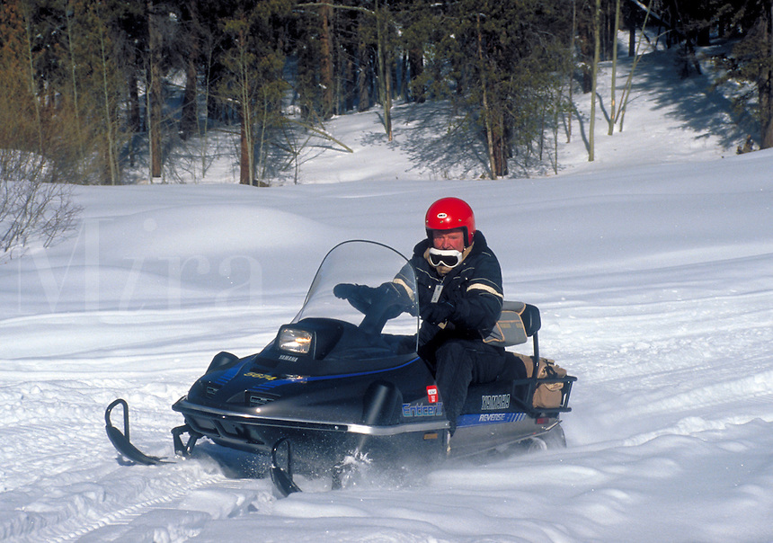 Winter scene. A senior man drives a snowmobile through the snowy plains in Vail. Vail Colorado.