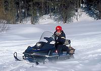 Winter scene. A senior man drives a snowmobile through the snowy plains in Vail. Vail Colorado.