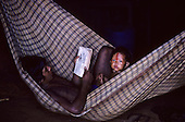A-Ukre, Brazil. A Kayapo Indian father with black genipapo body paint reading to his son in a hammock. Para State.