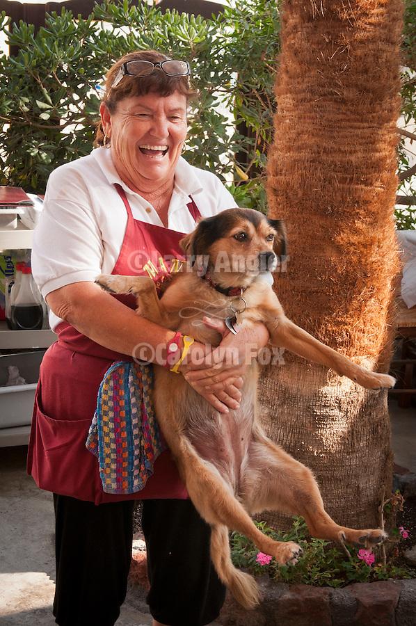 Mama's Restaurant, Fira, Santorini (Thira), Greece. Mama holds her favorite dog and smiles.