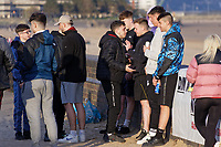 Pictured: Two young men appear to square up by the beach in Swansea Bay. Friday 16 April 2021<br /> Re: People enjoy an evening out after Covid-19 lockdown rules were relaxed, in Swansea Bay, Wales, UK.