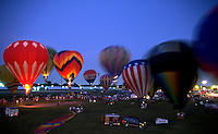 Hot air balloons gathered at a festival at night.