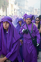 Antigua, Guatemala.  Cucuruchos Take Pictures too...; They have an Advantage.  Photographer accompanies a float, shrouded in the background in a cloud of incense, in a religious procession during Holy Week, La Semana Santa.