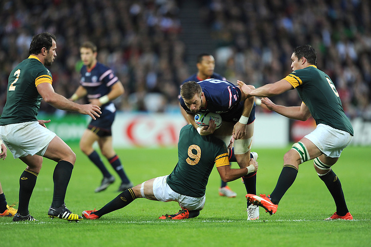 07 October 2015: Cam Dolan of USA is tackled by Fourie du Preez and Francois Louw of South Africa during Match 31 of the Rugby World Cup 2015 between South Africa and USA - Queen Elizabeth Olympic Park, London, England (Photo by Rob Munro/CSM)