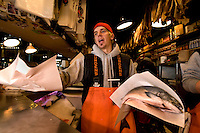 A worker wraps salmon at Pike Place Market in Seattle Washington.