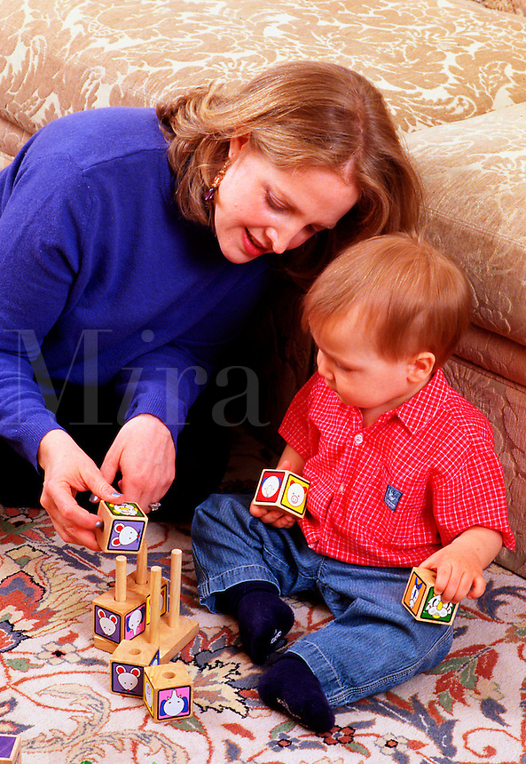 Mother and her toddler child play with toy blocks.