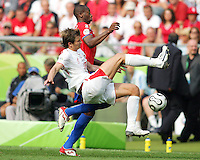 Mariusz Lewandowski (18) of Poland makes a flying tackle on Paulo Winchope (9) of Costa Rica. Poland defeated Costa Rica 2-1 in their FIFA World Cup Group A match at FIFA World Cup Stadium, Hanover, Germany, June 20, 2006.