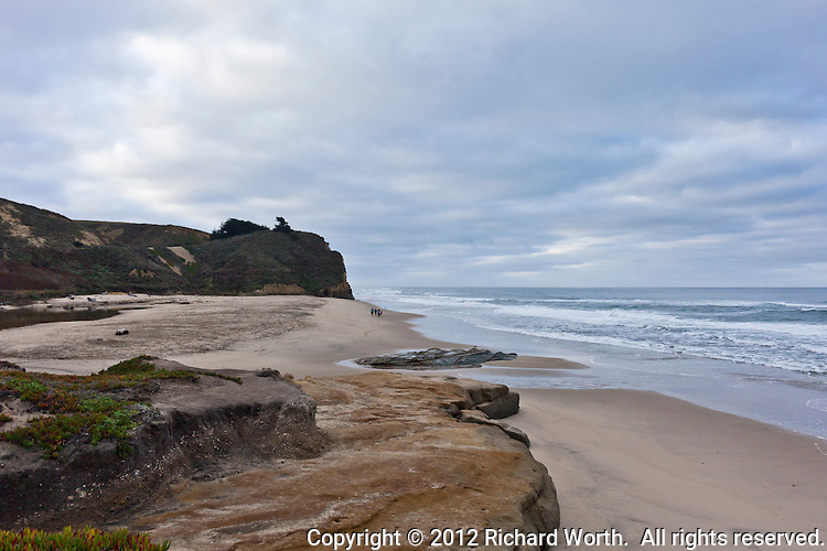 A group of visitors walking the sandy beach are little more than dots against the wide open landscape, seascape, at Pomponio State Beach on the California coast.