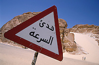 Road warning sign with White Sand Dune visible in the background, Sinai Desert, Dahab, Egypt.