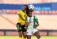 HOUSTON, TX - JUNE 10: Sashana Campbell #12 of Jamaica goes up for a header with Ijeoma Okonronkwo #5 of Nigeria during a game between Nigeria and Jamaica at BBVA Stadium on June 10, 2021 in Houston, Texas.