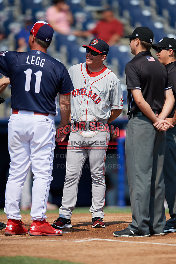 Portland Sea Dogs manager Darren Fenster (23) meets with manager Gregg Legg (11), home plate umpire Derek Thomas (not pictured), third base umpire Chris Marco and 1B umpire Derek Gonzales prior to the first game of a doubleheader against the Reading Fightin Phils on May 15, 2018 at FirstEnergy Stadium in Reading, Pennsylvania.  Portland defeated Reading 8-4.  (Mike Janes/Four Seam Images)