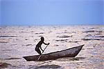 Man In Paddeling Dugout Canoe