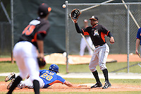 Miami Marlins first baseman Felix Munoz (46) waits for a pick off attempt throw as Colton Plaia (28) dives back safely during a minor league spring training game against the New York Mets on March 28, 2014 at the Roger Dean Stadium Complex in Jupiter, Florida.  (Mike Janes/Four Seam Images)