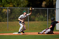 Dartmouth Big Green third baseman Connor Bertsch (23) catches a throw as Keil Krumwiede (11) slides in during a game against the Omaha Mavericks on February 23, 2020 at North Charlotte Regional Park in Port Charlotte, Florida.  Dartmouth defeated Omaha 8-1.  (Mike Janes/Four Seam Images)