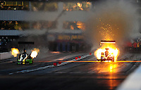 Feb. 19, 2010; Chandler, AZ, USA; NHRA top fuel dragster driver David Grubnic (right) explodes an engine alongside Steve Torrence during qualifying for the Arizona Nationals at Firebird International Raceway. Mandatory Credit: Mark J. Rebilas-