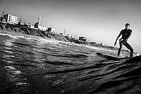 21 year old surfer Mahmoud Alyrashi rides a wave in the Mediterranean Sea off Gaza City.