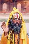 This sadhu, or holy man, has an intricate tilaka painted on his forhead. These markings indicate which Hindu god he follows. His raised hand is a gesture of blessing.