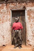Africa, Swaziland, Malkerns. Nest organization artisan project.Wmen in front of her round thatched house.