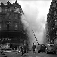 """Edifice commercial et de bureaux, magasin """"Au gaspillage"""" au début du XXe siècle, """"Au bon marché de Paris, """"le Printemps"""" et les assurances """"Le continent"""" dans les années 1960, """"Bouchara"""", """"Zara"""", 47 rue d'Alsace-Lorraine. 11 Mars 1964. Vue de l'incendie de l'immeuble du Printemps et de l'intervention des pompiers : vue prise depuis la rue d'Alsace ; l'immeuble ravagé par le feu, entouré de nuages de fumée épaisse, des badauds dont un photographe, cigarette à la bouche, regardant en direction de l'appareil photo ; la grande échelle au second plan. L'incendie semble maîtrisé."""