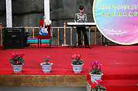 China. Jilin Province. A woman playing the keyboard in an agricultural shopping centre in the town of Yanji, close to the border with North Korea. The town is part of the Korean Autonomous Prefecture in the north-east of the country. 2011