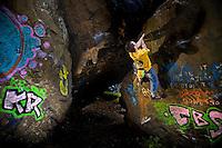 Bouldering on the graffiti covered rock at Dumbarton, Scotland