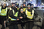 © Joel Goodman - 07973 332324 . 05/11/2016 . London , UK . Police detain , handcuff and carry away a woman from the protest in Trafalgar Square . Supporters of Anonymous , many wearing Guy Fawkes masks , attend the Million Mask March bonfire night demonstration , in central London . Photo credit : Joel Goodman